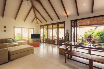 Luxury villa living room with kitchen interior. White walls and wooden furniture