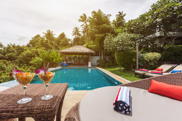 Fruit salads on table on private swimming pool near luxury villa. Sunny summer vacation