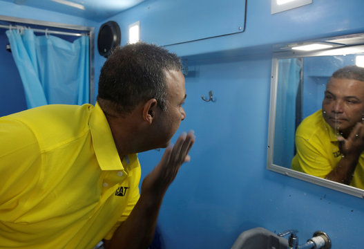 A homeless man looks in a mirror after bathing in a bus equipped with showers, which is part of Pro Mundo Foundation's project for people living on the streets, in San Jose, Costa Rica