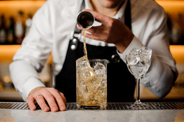 Barman hand pouring a portion of alcoholic drink into a glass