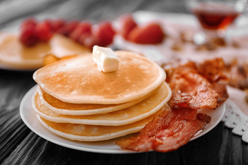 Plate with pancakes and bacon on table, closeup