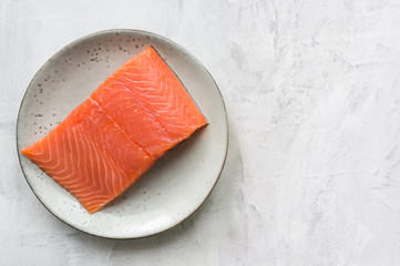 Fresh salmon steak on rustic plate. Top view.