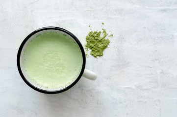 Creamy drink, matcha latte on concrete background. Top view. Traditional japanese green tea powder.