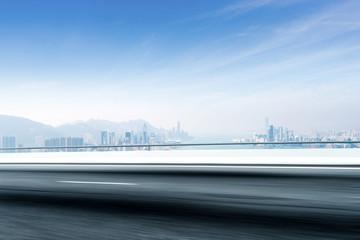 blurry empty asphalt road with modern cityscape