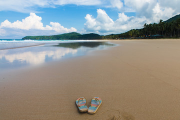 pair of flipflops in empy sand beach with cloudy sky and tropical trees on background