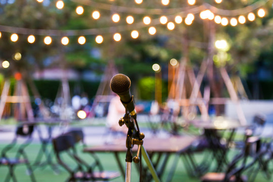 Microphone stand for the singer with the light hanging and table set for party in the park background