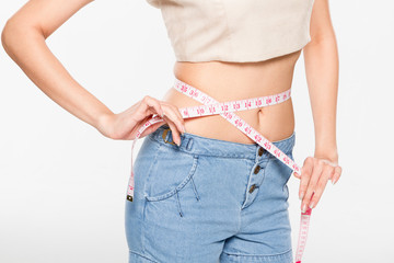 Close Up Woman measuring her waistline with measure line