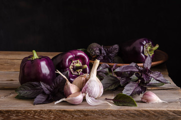 Dark purple peppers with leaves of basil and garlic on old rustic wooden table on black background.