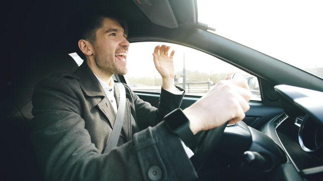 Happy handsome businessman driving car and singing. Man is happy after making deals and drives home