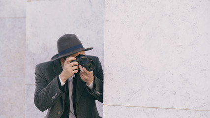 Closeup of young paparazzi man in hat photographing celebrities on camera while spy behind the wall