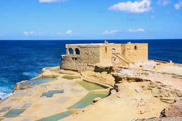 Salt pans along the waterfront with the Il-Qolla I-Badja battery to the rear, Marsalforn, Gozo, Malta.