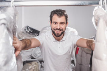 dry cleaning worker at warehouse with clothing packed in plastic bags