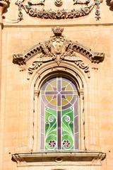 Ornate stained glass window on the front of Naxxar Parish church, Naxxar, Malta.