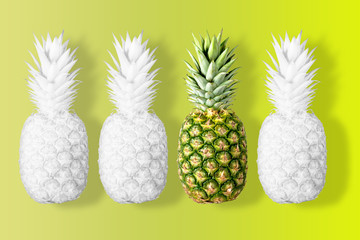 White colored pineapples on a vivid yellow background. Minimal concept.