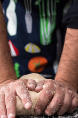 Male hands kneading dough, baking preparation closeup.