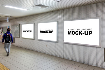 Three mock up billboards on the wall at corridor inside train station