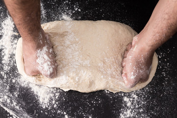 Male hands kneading dough, baking preparation closeup.