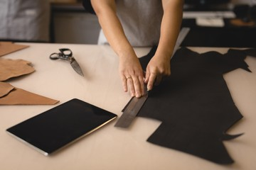 Worker measuring leather with ruler in workshop