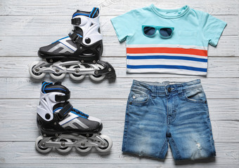 Roller skates, clothes and sunglasses on white wooden background