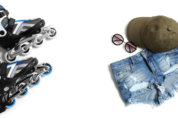 Roller skates, clothes and sunglasses on white background