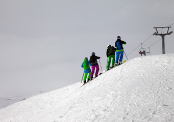 Skiers on snowy off-piste slope and overcast misty sky