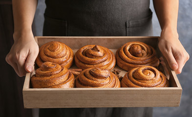 Woman holding wooden tray with sweet cinnamon rolls