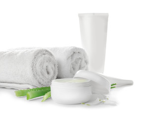 Jar with body cream, towels and aloe leaves on white background