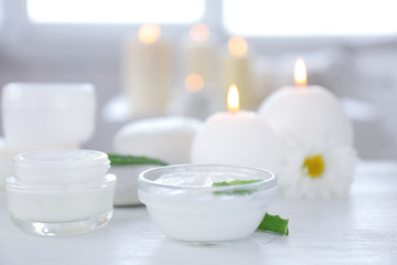 Bowl with body cream and aloe leaves on table
