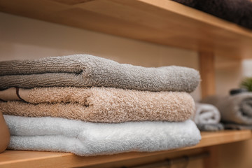 Soft towels on wooden shelf indoors, closeup