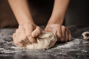 Woman kneading dough on table