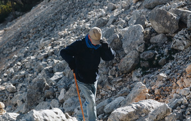 Aged man hiking in the trail to Gola su gorroppu - activity and health concept