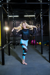 A sporty girl with beautiful long hair is photographed in the gym