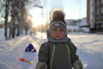 baby winter Romper, hat with a large fluffy POM-POM, scarf, mittens is standing on a footpath in winter alley in back light