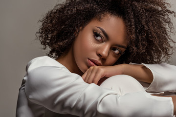 Young sensual african american woman in white shirt looking away isolated on grey background