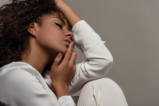 Young tender african american woman in white shirt touching lips isolated on grey background