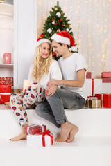 Photo of couple in love with Santa caps and pajamas
