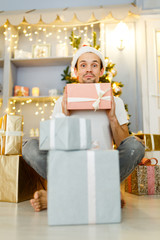 Image of men in Santa caps with gift in box and pajamas