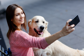 Photo of woman on bench doing selfie with dog
