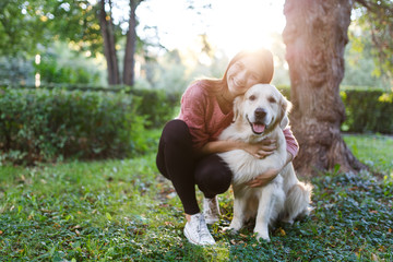 Photo of woman hugging dog on lawn