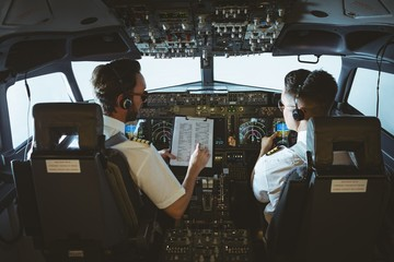 Pilot and copilot discussing over clipboard