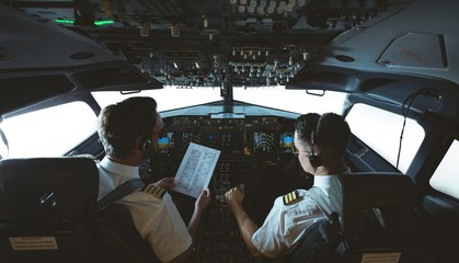 Pilot and copilot looking at instruction list in airplane