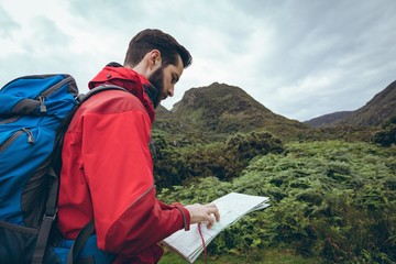 Male hiker reading the map near the green hills