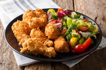 Fried chicken wings in breadcrumbs and fresh vegetable salad close-up. horizontal