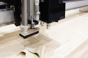 CNC machine for cutting fabrics textile materials and leather, laser marking and measurement. Modern footwear production.