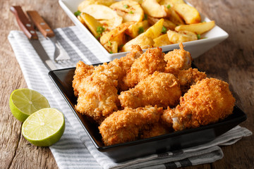 Delicious food: deep-fried chicken wings in breadcrumbs and potato close-up. horizontal