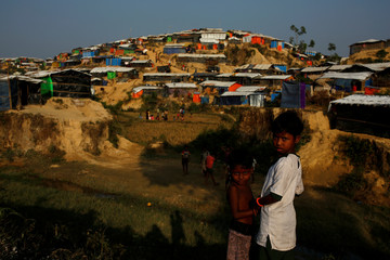 Two Rohingya refugee girls stand on a hill at the Jamtoli refugee camp near Cox's Bazar