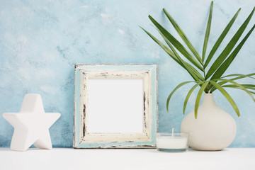 Square blue Photo frame mock up with green tropical plants in vase, ceramic star and candle on shelf. Scandinavian style. Text space