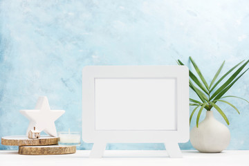 White Photo frame mock up with plants in vase, ceramic decor on shelf on blue background. Scandinavian style. Text space