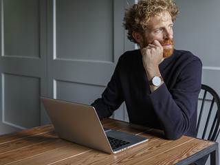 Thoughtful man with laptop sitting indoors