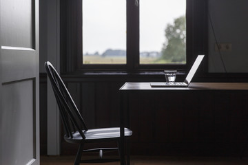 Wooden table with laptop computer in a design country house.